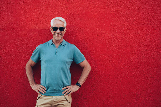 Confident mature man standing on red background Portrait of confident mature man standing his hands on hips against red background. akimbo stock pictures, royalty-free photos & images