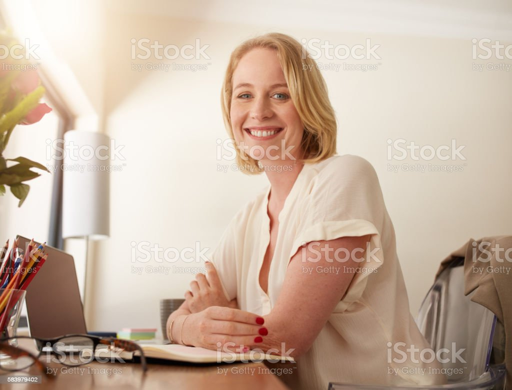 Confident mature woman sitting at working desk - foto de acervo