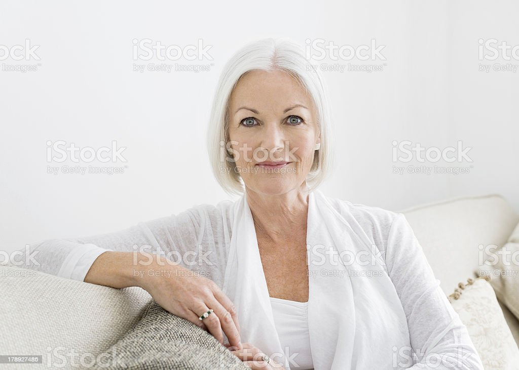 Confident Mature Woman Sitting On Sofa stock photo