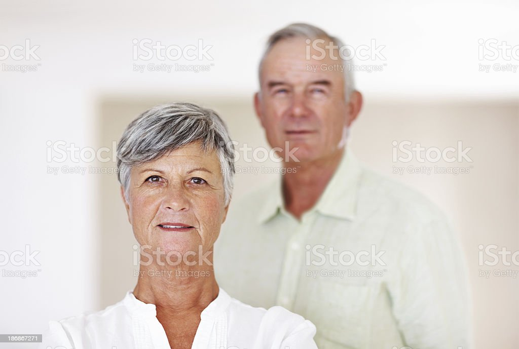 Confident mature woman with man in background royalty-free stock photo