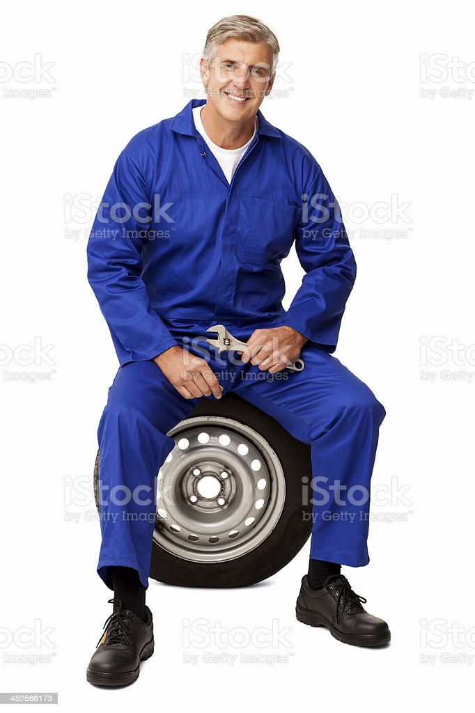 Confident Mechanic With Wrench Sitting On Tire stock photo