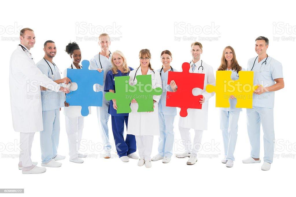 Confident Medical Team Holding Jigsaw Pieces - Lizenzfrei Afrikanischer Abstammung Stock-Foto