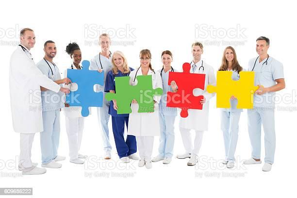 Confident Medical Team Holding Jigsaw Pieces Stockfoto und mehr Bilder von Afrikanischer Abstammung