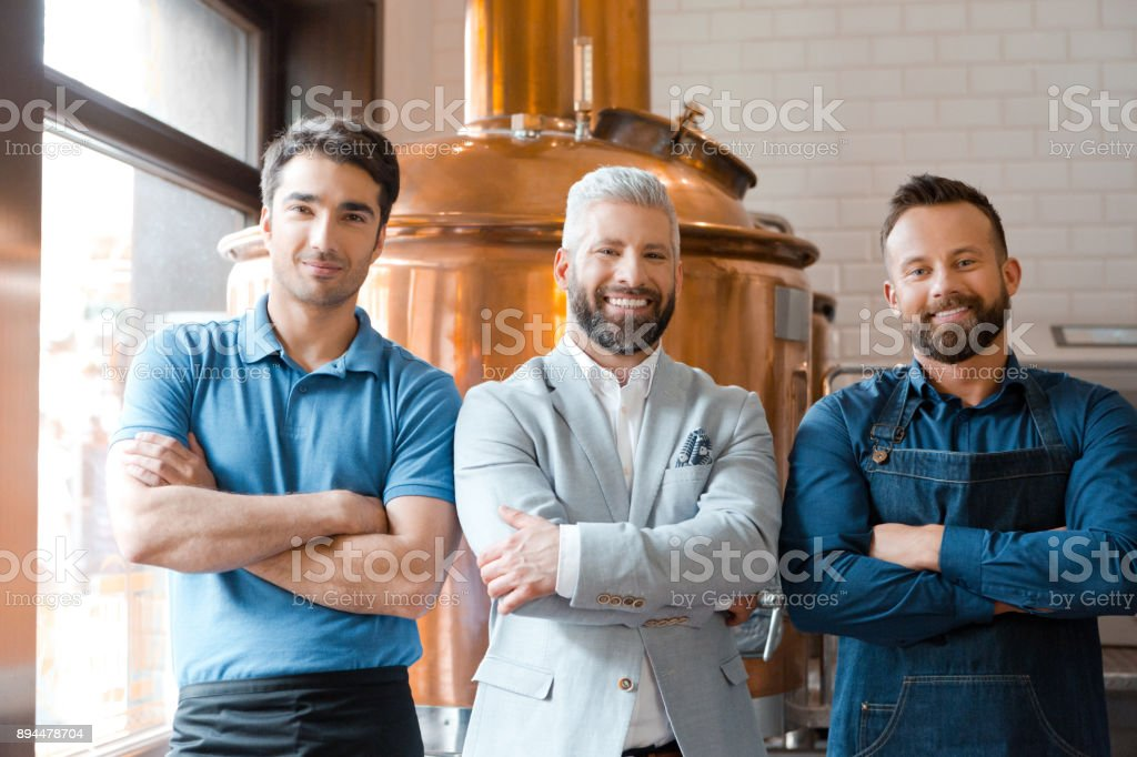 Confident microbrewery team standing together Portrait of confident microbrewery team standing together with arms crossed and looking at camera. Adult Stock Photo