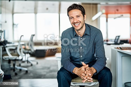 Portrait of confident mid adult businessman. Smiling male professional is sitting with hands clasped. He is in formals at office.