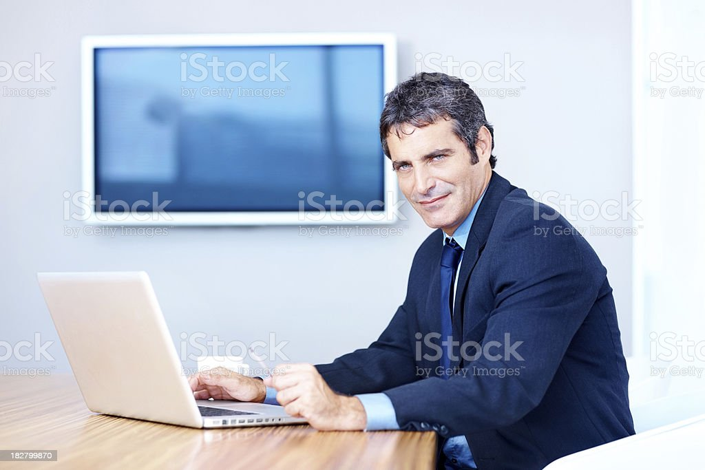 Confident mid adult businessman using a laptop royalty-free stock photo
