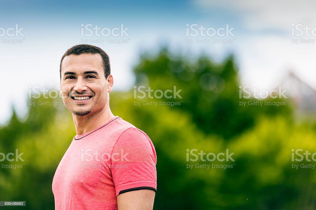 Confident mid adult jogger smiling in park stock photo