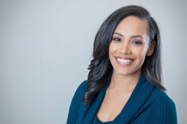 Confident mid adult mixed race woman Cheerful mixed race mid adult woman smiles confidently at the camera. Copy space available. one mid adult woman only stock pictures, royalty-free photos & images