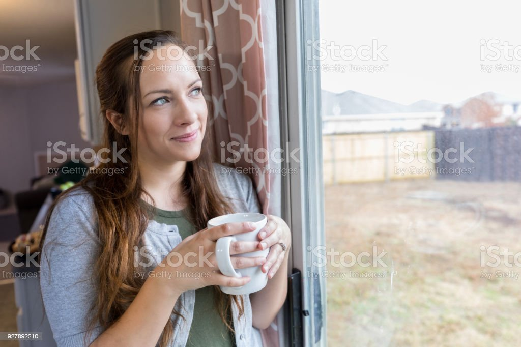 Beautiful mid adult Caucasian woman smiles while day dreaming in her...