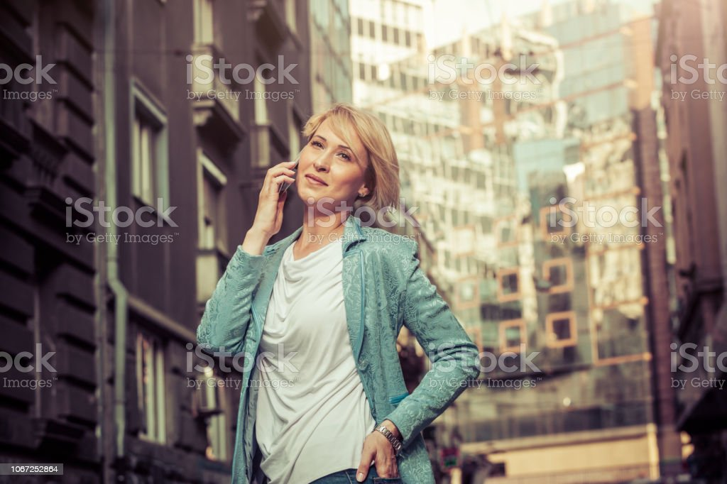 Confident mid-age woman talking on a mobile phone in the street stock photo