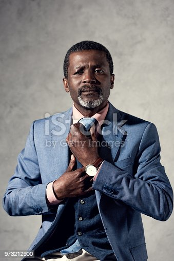 973213156 istock photo confident middle aged african american businessman fixing tie 973212900
