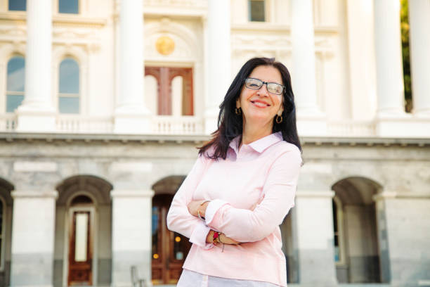 Confident Middle aged beautiful smiling Latina woman portrait by government building Confident Middle aged beautiful smiling Latina woman portrait by government building, arms crossed.. civil servant stock pictures, royalty-free photos & images