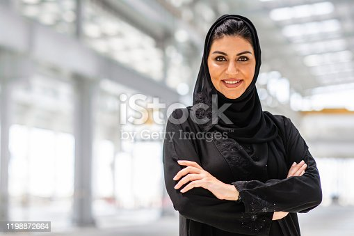 Portrait of smiling Abu Dhabi female design professional wearing traditional Islamic clothing and smiling at camera with arms crossed at construction site.