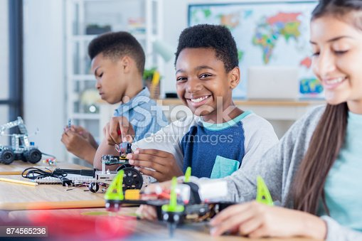 1016655140 istock photo Confident middle school boy works on engineering project 874565236