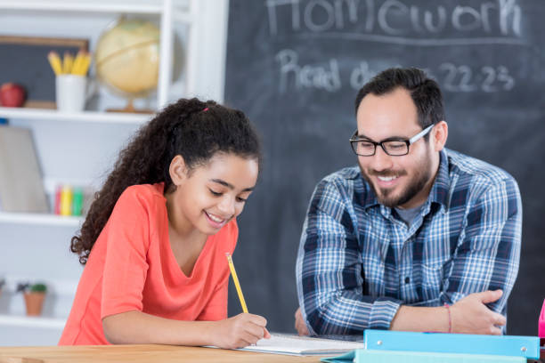 Confident middle schoolgirl works on assignment stock photo