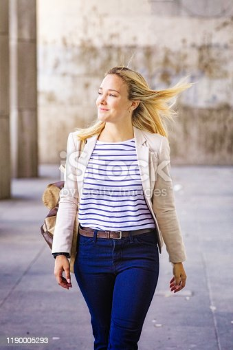 Confident millennial female business person smiling outdoors walking fast, feeling the wind in her hair.