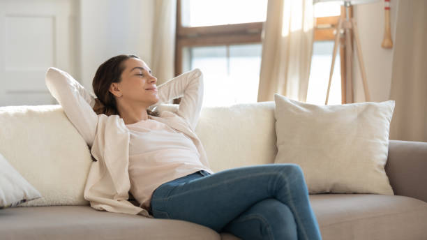 Confident millennial female enjoying tranquility relaxing on sofa indoors stock photo