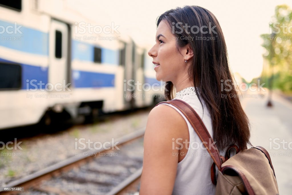 Confident millennial student on the go checking her smart phone on a train platform stock photo