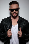 Confident model fixing his leather jacket while wearing sunglasses, standing on gray studio background