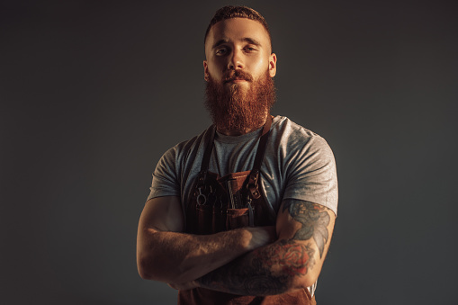Contemporary bearded lumbersexual hairdresser crossing arms and looking at camera against gray background
