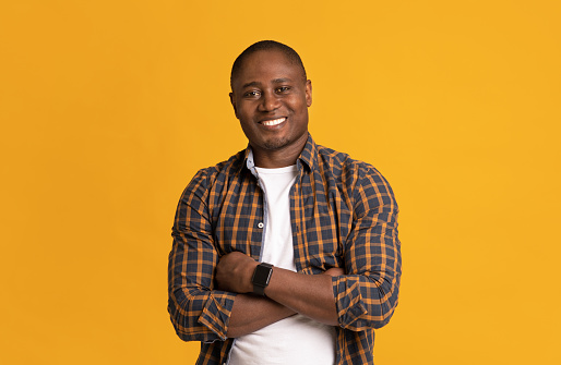Confident modern man in casual clothes look at camera. Calm smiling mature attractive african american man in plaid shirt with crossed arms on chest, isolated on yellow background, studio shot