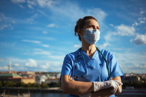 confident modern physician woman outdoors in city against sky stock photo