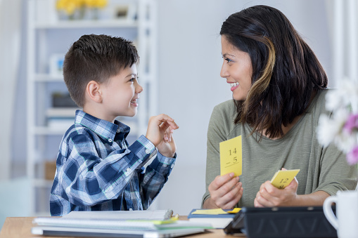 Confident mom reviews flashcards with son