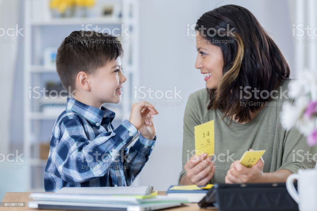 Confident mom reviews flashcards with son stock photo