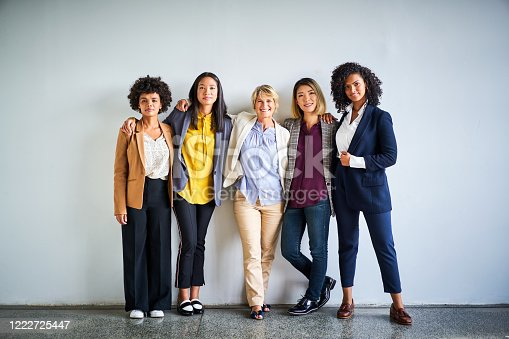 Portrait of confident female professionals. Smiling multi-ethnic businesswomen standing together. They are against wall at office.