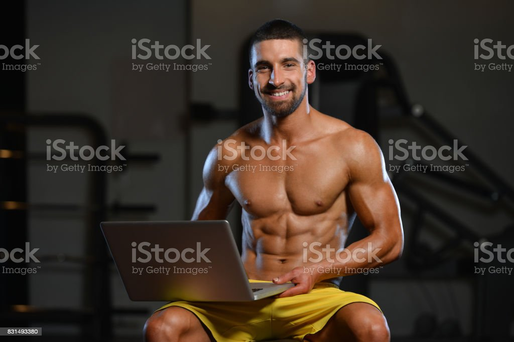 Confident Muscled Man In Gym Using Laptop stock photo