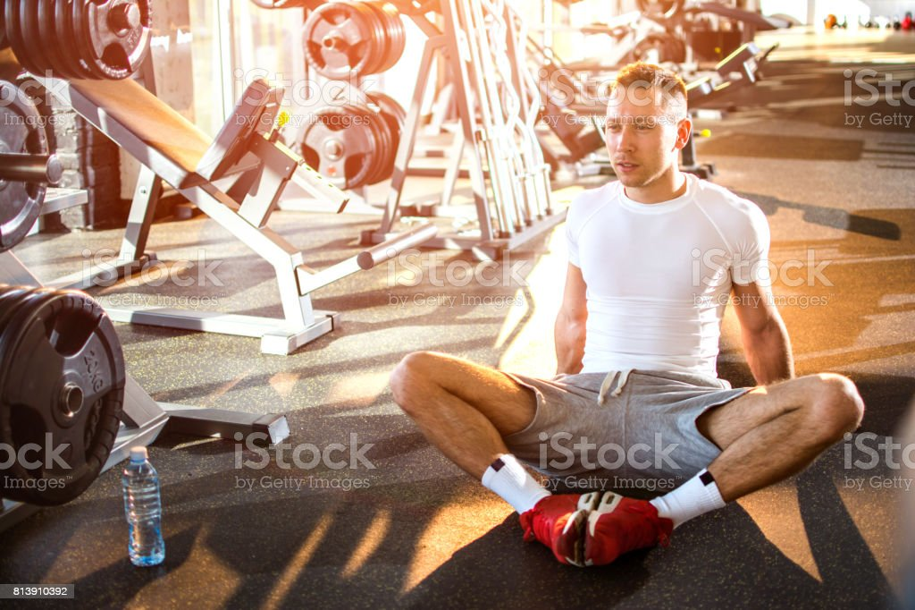 Confident muscled young man stretching in gym. stock photo
