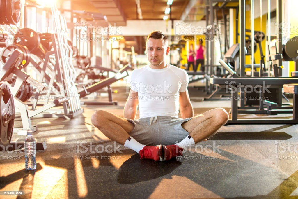 Confident muscled young man wearing sport wear and sitting on the floor at gym. Resting time. stock photo