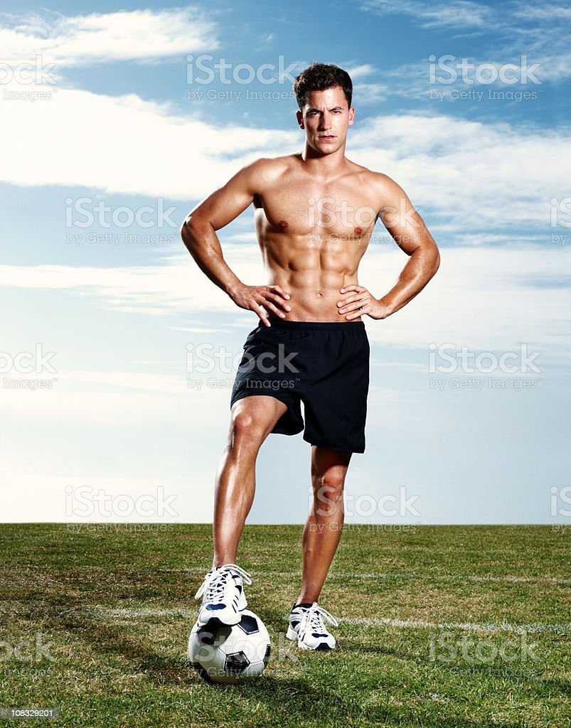Confident muscular guy with football standing on field