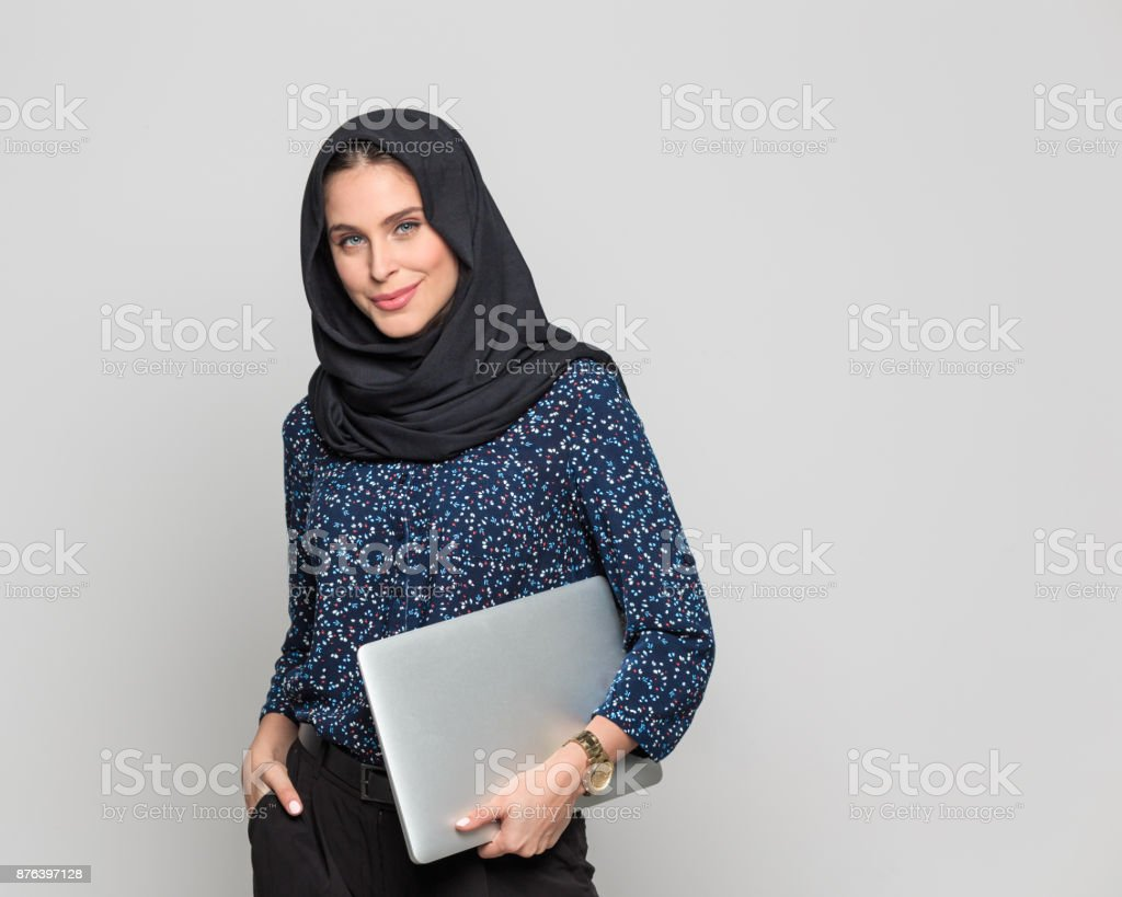 Confident muslim businesswoman with a laptop Portrait of confident young muslim woman holding a laptop against grey background. Businesswoman in hijab with laptop computer looking at camera. 20-29 Years Stock Photo