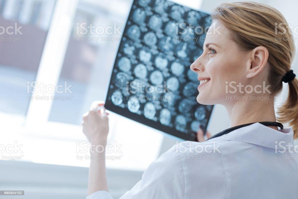 Confident neurosurgeon analyzing roentgen brain results at the laboratory stock photo