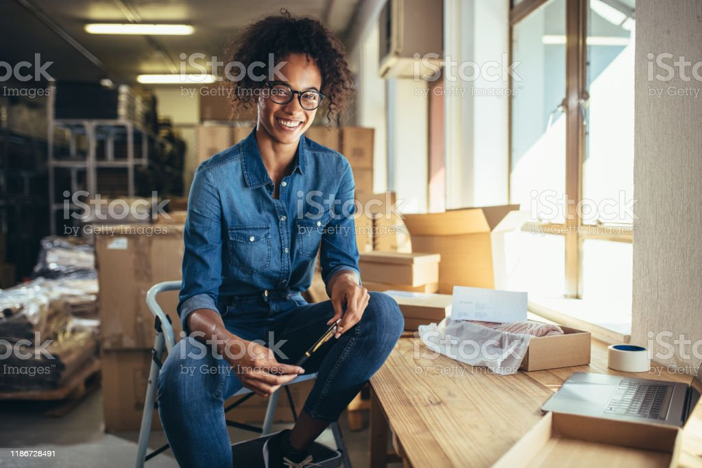 Confident online business owner Smiling young woman sitting at her workplace. Confident online business owner looking at camera and smiling. Adult Stock Photo