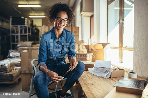 Smiling young woman sitting at her workplace. Confident online business owner looking at camera and smiling.