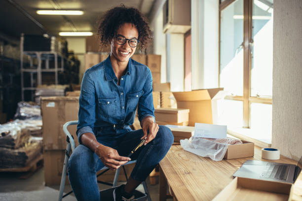 Confident online business owner Smiling young woman sitting at her workplace. Confident online business owner looking at camera and smiling. jacoblund stock pictures, royalty-free photos & images