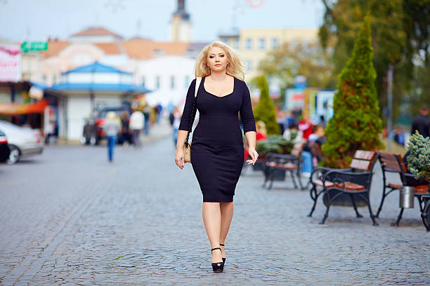 confident overweight woman walking the city street - curvy voluptuous women stock photos and pictures
