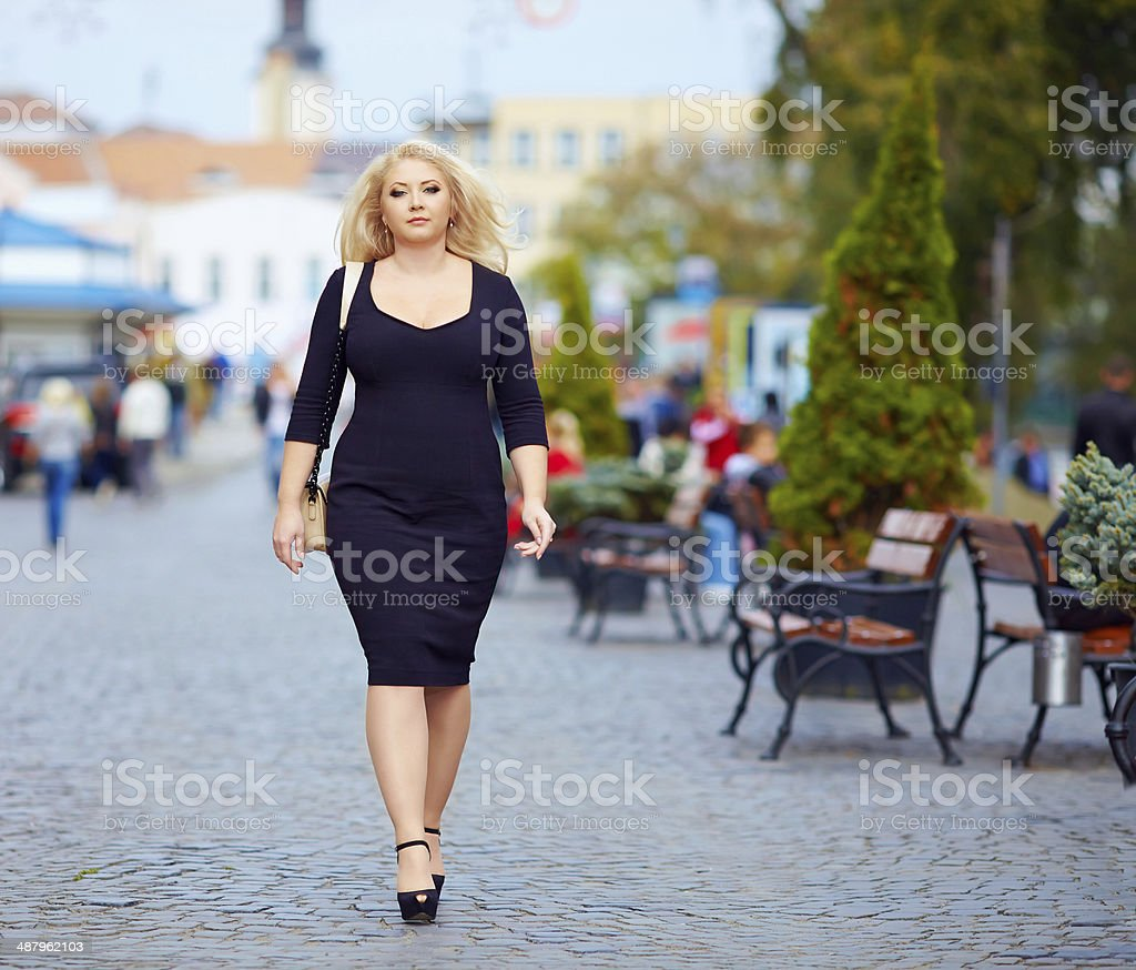 confident overweight woman walking the city street stock photo