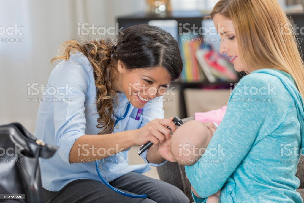 Confident pediatrician examines newborn baby during house call stock photo