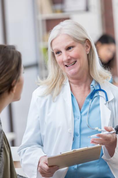 zuversichtlich arzt erklärt etwas patientin - symptome brustkrebs stock-fotos und bilder