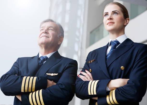 Confident pilots looking through the window Cabin Crew, Pilot, Co-Pilot, Adult pilot stock pictures, royalty-free photos & images