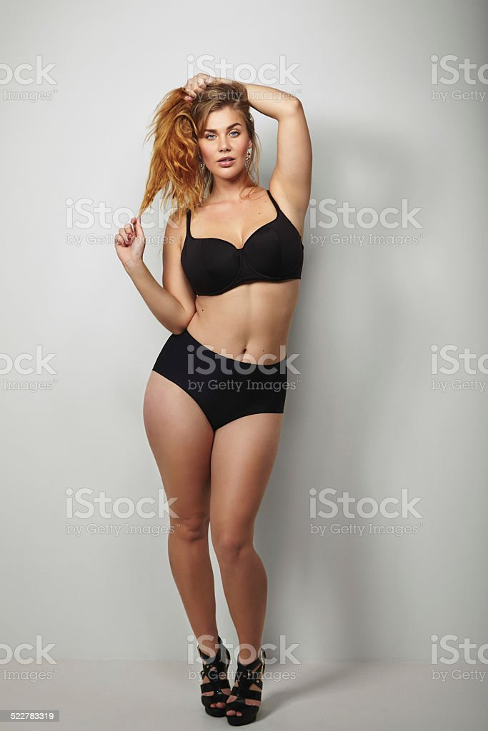 Confident plus size woman posing in bikini stock photo
