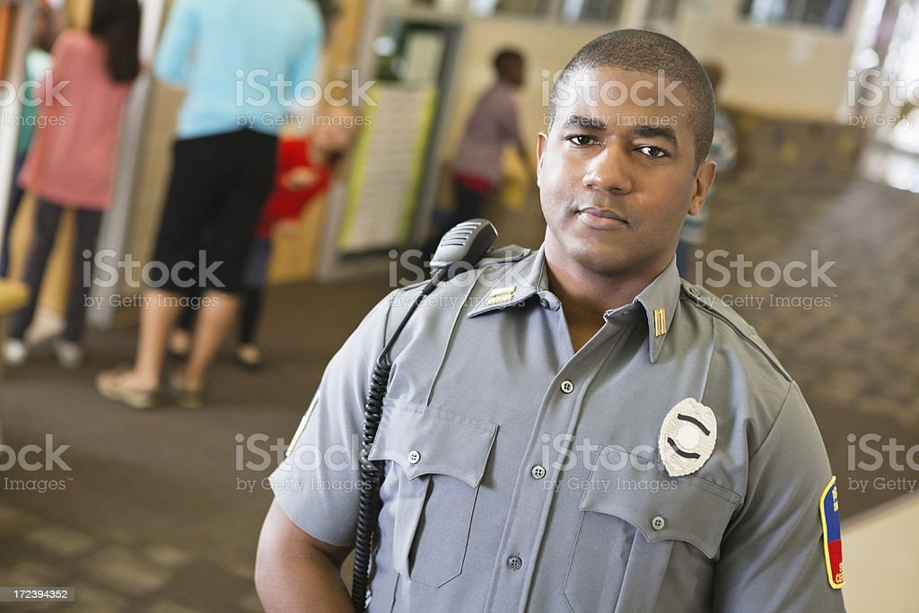 Confident police officer in elementary school hallway stock photo