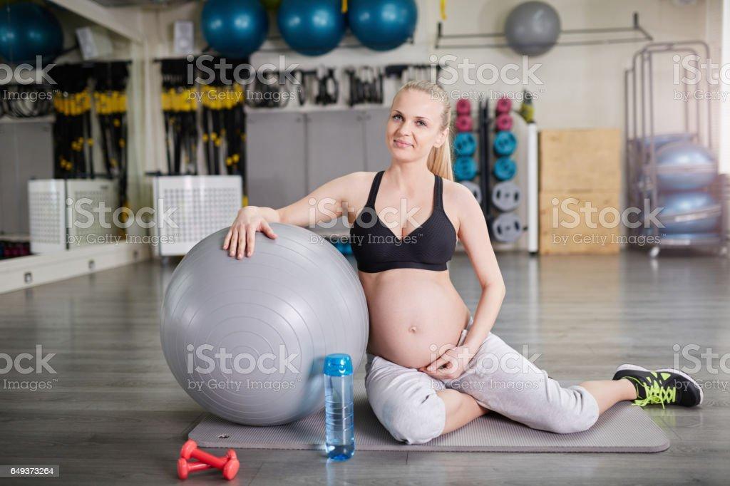 Vertrouwen zwangere vrouw zit op sportschool met pilates bal foto