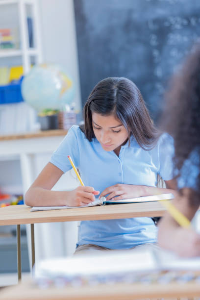 Confident preteen student takes notes in class Hispanic girl takes notes during class. She is writing in a spiral notebook. cute middle school girls stock pictures, royalty-free photos & images