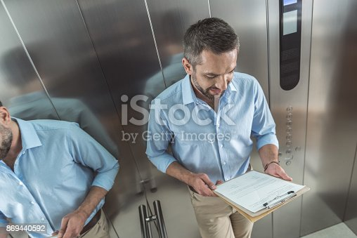 Important papers. Top view of charming bristled man in casual clothes is standing in elevator and holding documents while reading with concentration