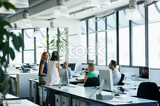 Team of confident professionals discussing in office