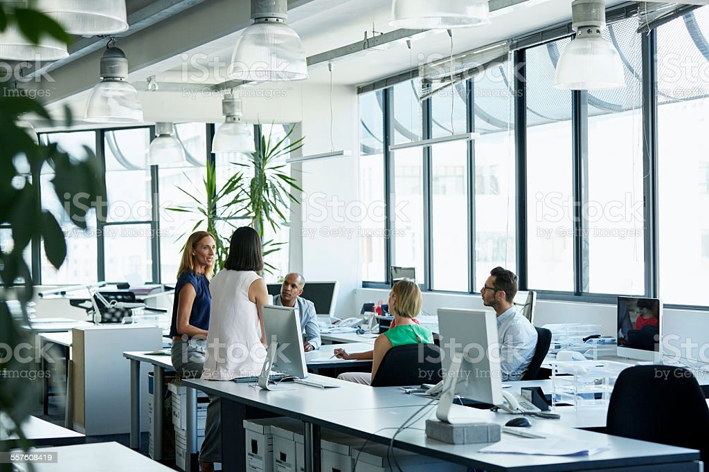 Confident professionals discussing in office stock photo